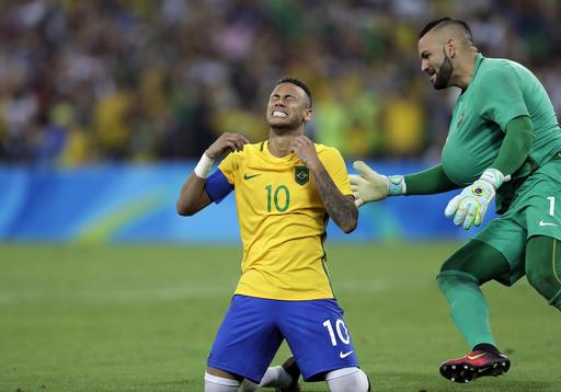 Brazil's Neymar cries as he kneels down to celebrate with teammate goalkeeper Weverton